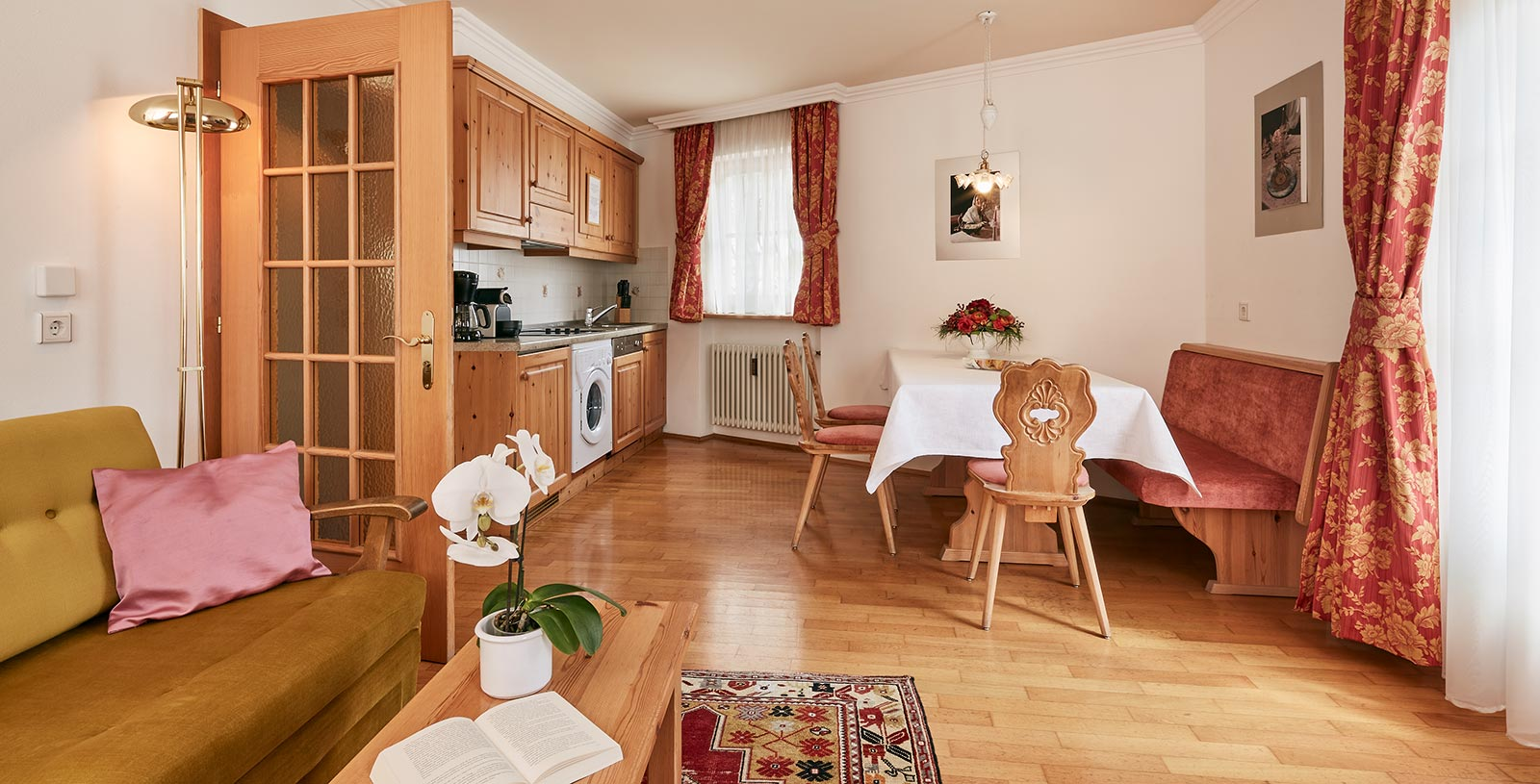 Kitchen-cum-living room of a holiday apartment of the Chalet Cristina with typical wooden bench