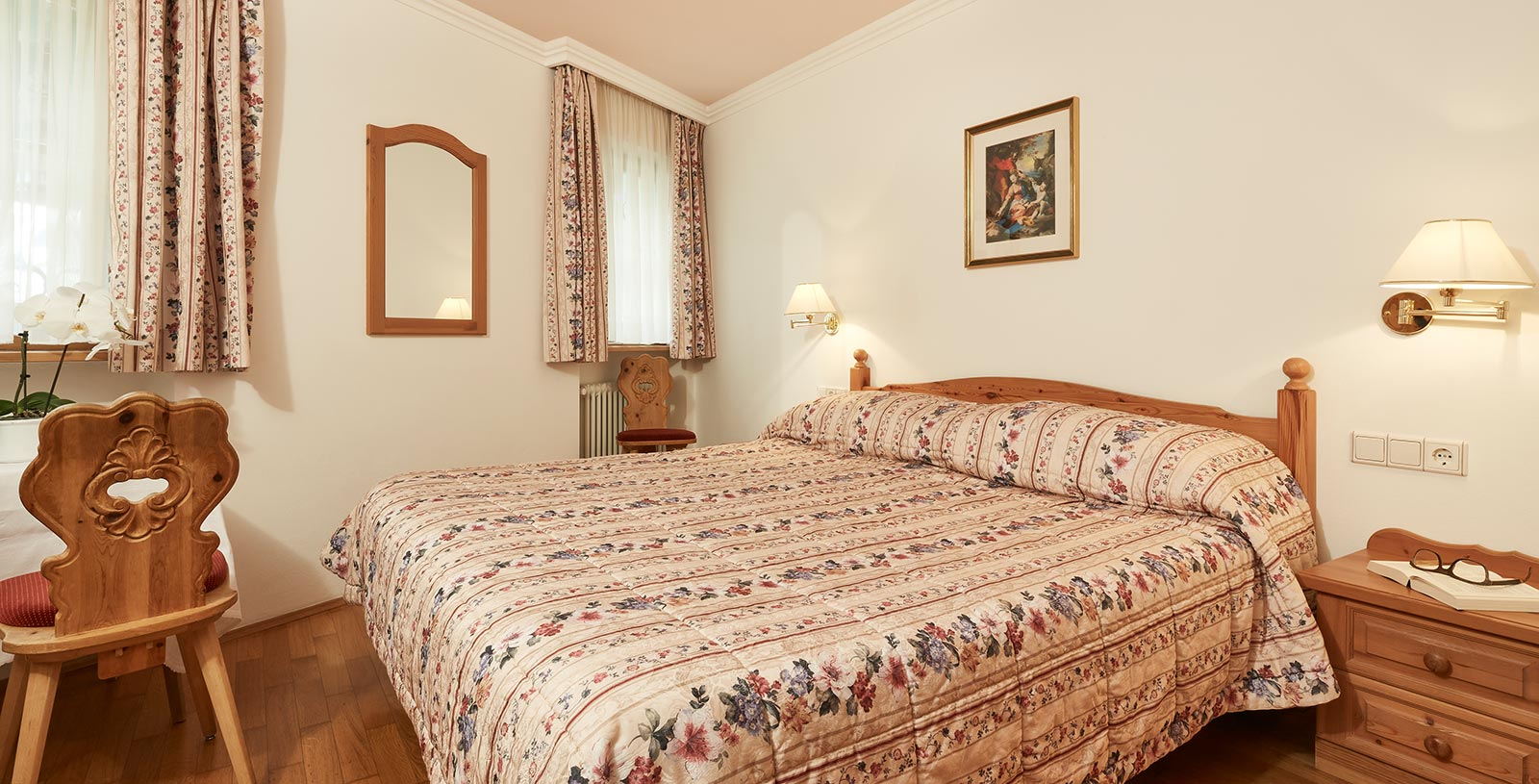 the kingsize bed of a vacation home in Corvara, curtains and bed linen wear the same flower motif